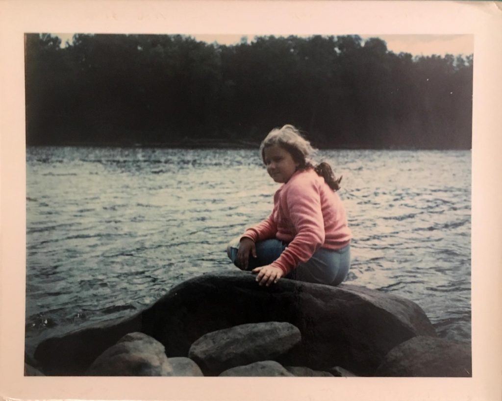 white girl about 11 sitting on rock by the water